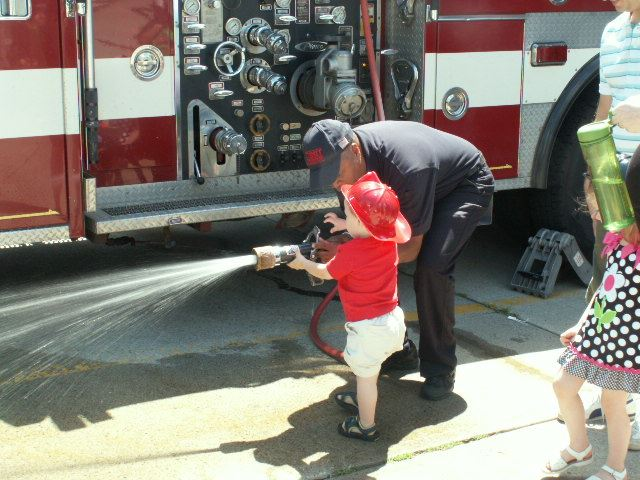 Small child learning how to hold fire hose