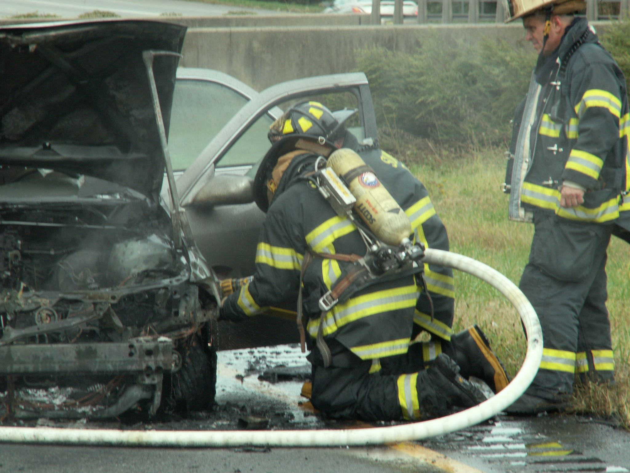 Firefighter kneeling next to car